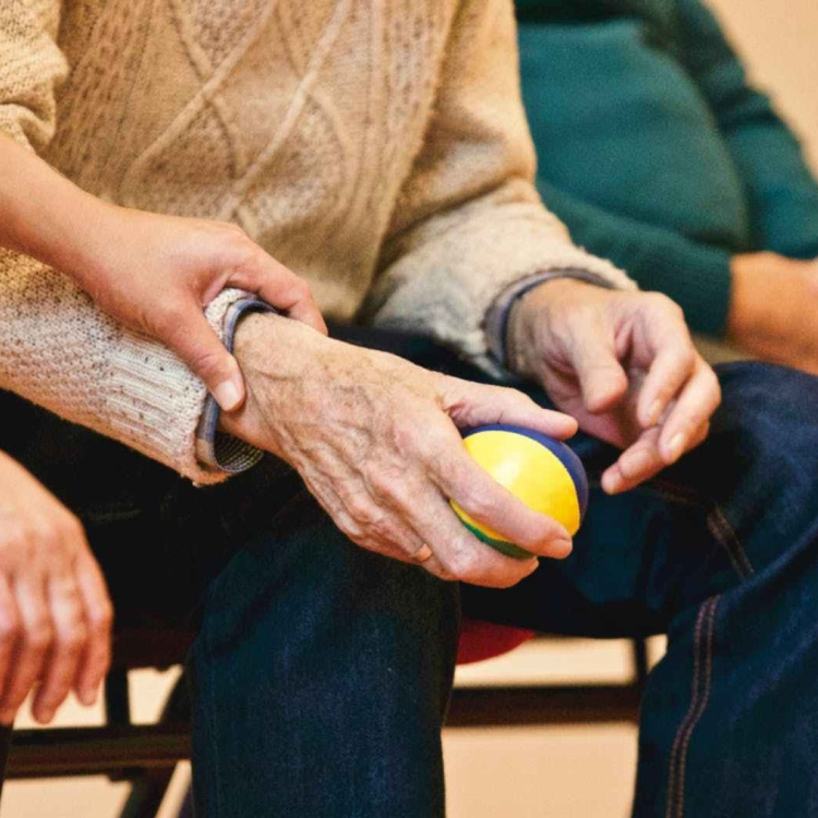 Elderly person holding ball