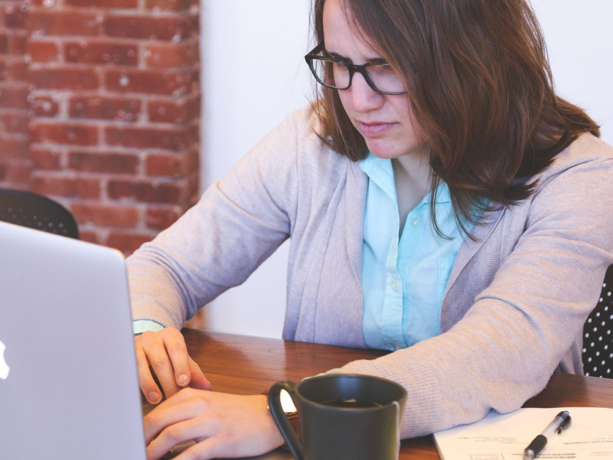 women frowning over laptop, with cup of tea and notebook