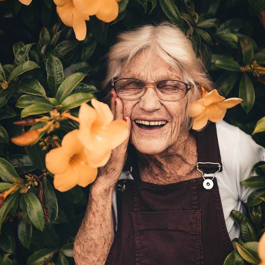 older woman smiling amongst flowers