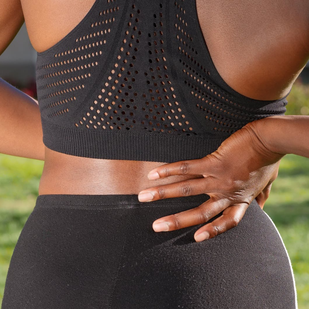 Black women holds her back as though in pain. She is wearing black active wear.